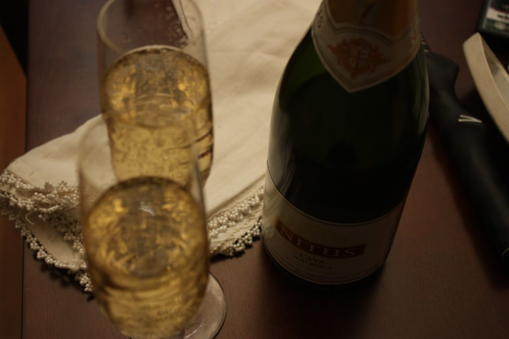 two champagne glasses, a bottle and a beaded napkink on a tabletop