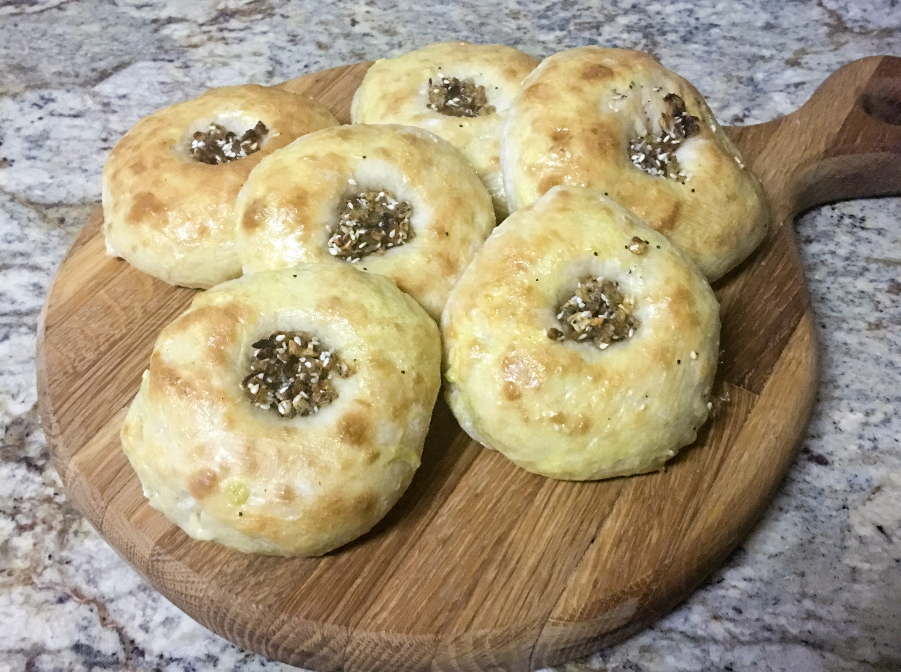 Bialy or Bialystoker Kuchen topped with onion, garlic, sesame and poppy seeds