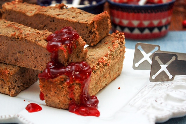stacked slices of Polish pate topped with red lingonberry jam, Polish pottery in the background