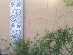 talavera tile design stenciled on a cement block wall with plants in foreground