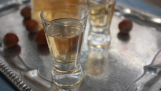 hazelnut liqueur in shot glasses on a silver tray with whole hazelnuts and a bottle in the background