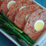 slices of Polish meatloaf stuffed with egg in a baking dish with asparagus on the side