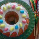 polish easter babka on green cake plate topped with a white glaze and candy eggs