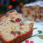 Polish fruitcake with tea on a holiday napklin in front of a christmas tree