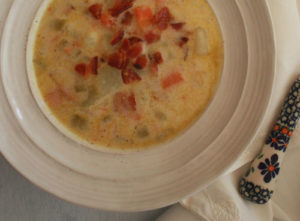 Polish potato soup in a white bowl topped with crumbled bacon