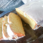 a loaf of cheese babka and three slices on a dark platter with glass plate and forks in the backgorund