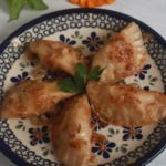 Pork pierogi friend with onions on a Polish pottery plate with colorful flowers in the background