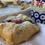 Polish poppy seed danish on a cloth napkin beside a Polish pottery mug