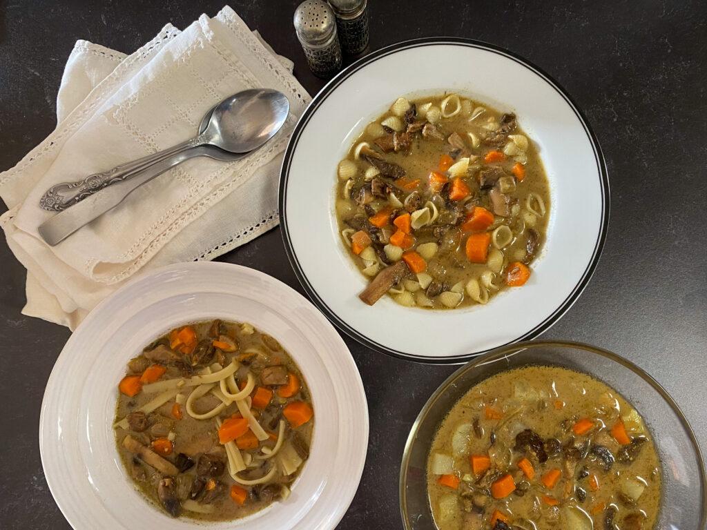 3 bowls of Polish mushroom soup on a dark countertop