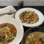 3 bowls of Polish mushroom soup on a dark countertop.