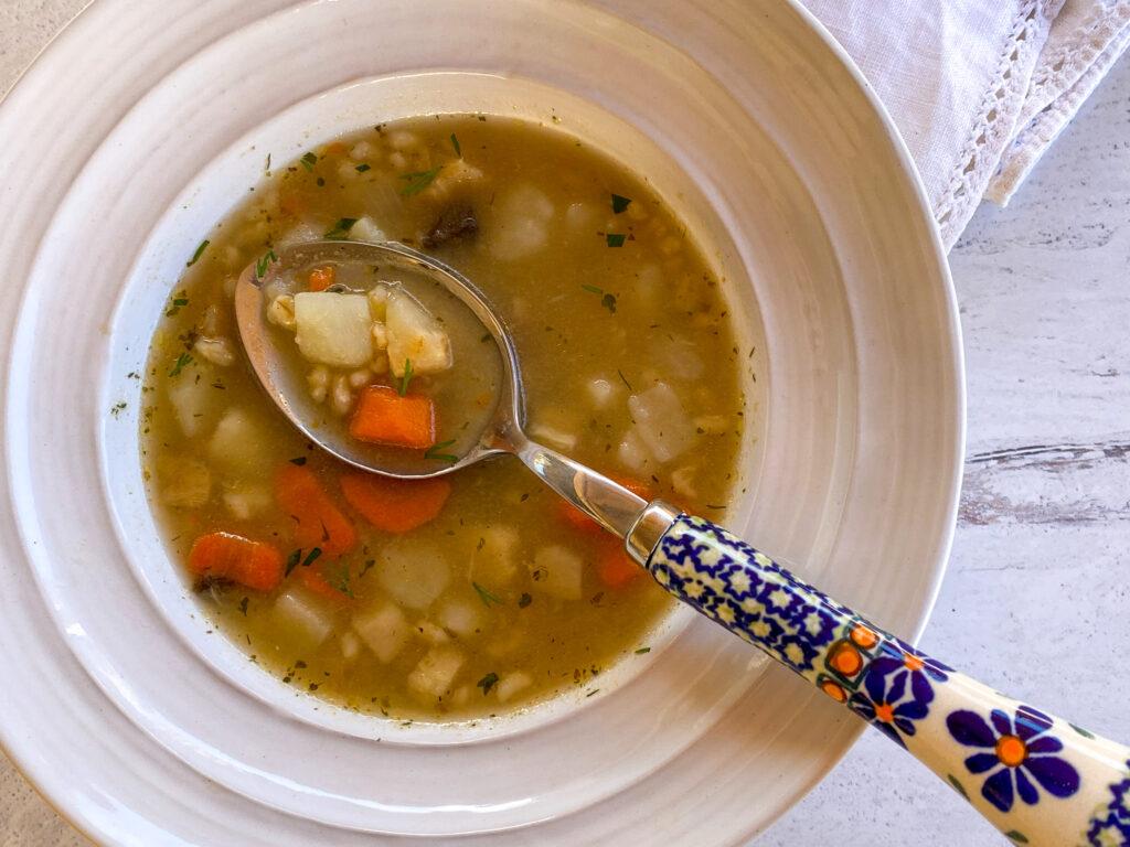 Polish krupnik soup in a white bowl